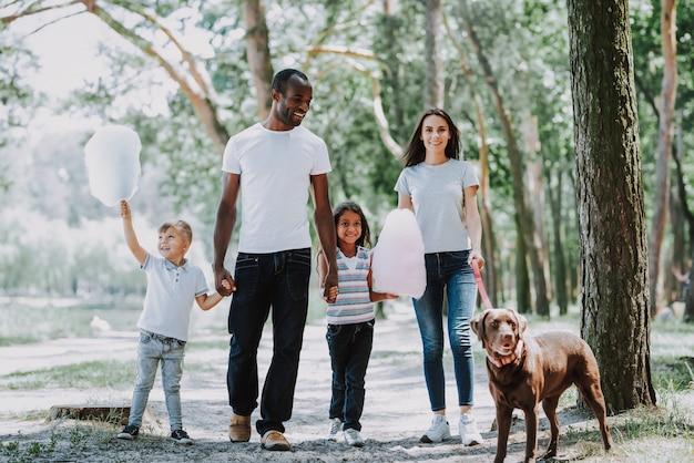 Ouders en kinderen lopen door park met hond Premium Foto