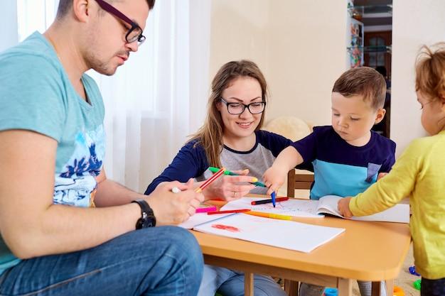 Ouders en kinderen tekenen samen in de kamer Premium Foto