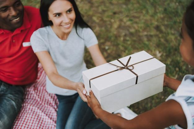 Ouders geven een klein meisje een cadeau in hout. Premium Foto