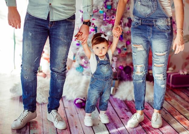 Ouders houden dochterhanden in de kamer met de chirstmas-boom Gratis Foto
