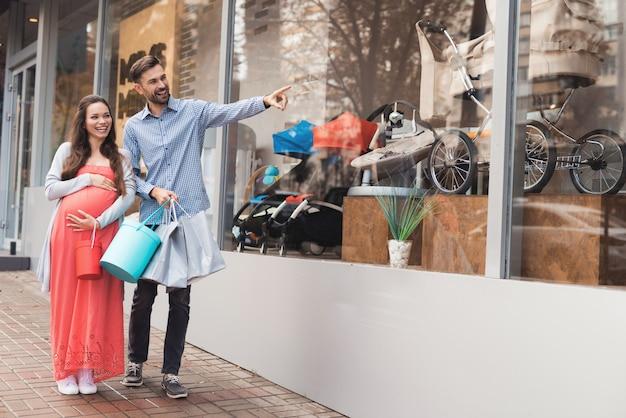 Ouders komen naar het winkelcentrum en kiezen dingen voor het toekomstige kind. Premium Foto