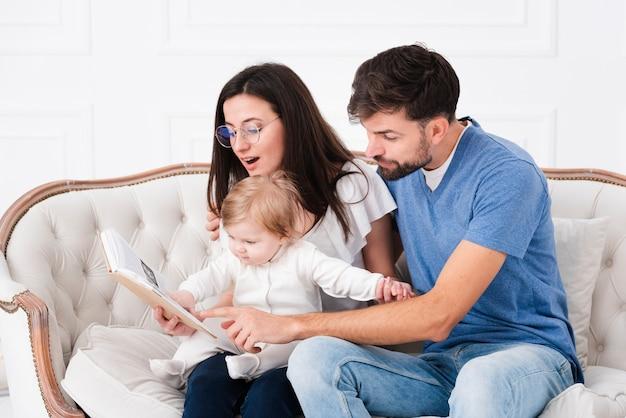 Ouders lezen terwijl ze baby vasthouden Gratis Foto