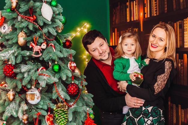 Ouders met een klein blond meisje poseren voor een kerstboom in de kamer Gratis Foto