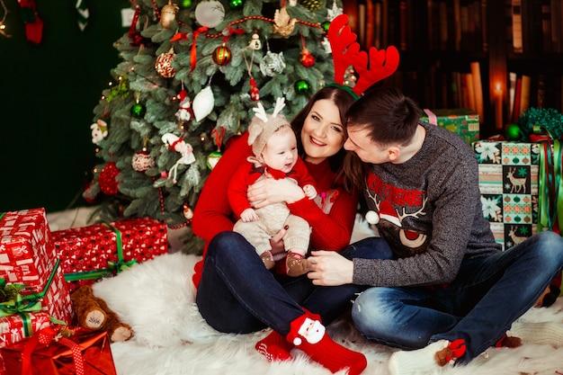 Ouders spelen met dochtertje in hertenhoed die haar op hun armen houdt en voor een kerstboom zit Gratis Foto
