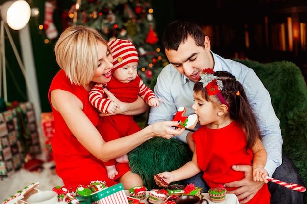 Ouders spelen met hun twee kinderen aan de tafel voor de groene kerstboom Gratis Foto