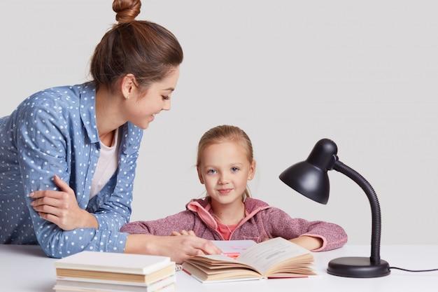 Ouderschap, studeren en onderwijs concept, blauwe ogen vrouwelijke kind zit op de werkplek, leest samen met moeder boek, leert gedicht uit het hoofd, pose in gezellige kamer op wit Gratis Foto
