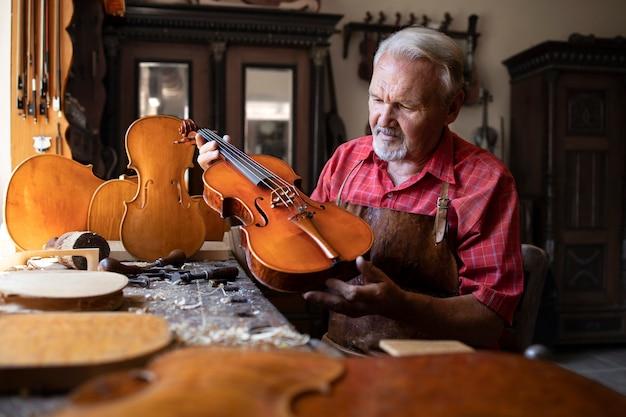 Ouderwetse houtbewerker die zijn meesterwerk vasthoudt en bewondert Gratis Foto
