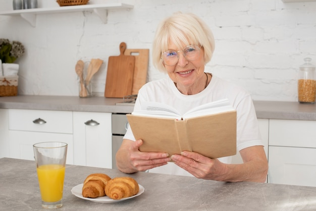 Oudste die een boek in de keuken houdt Gratis Foto
