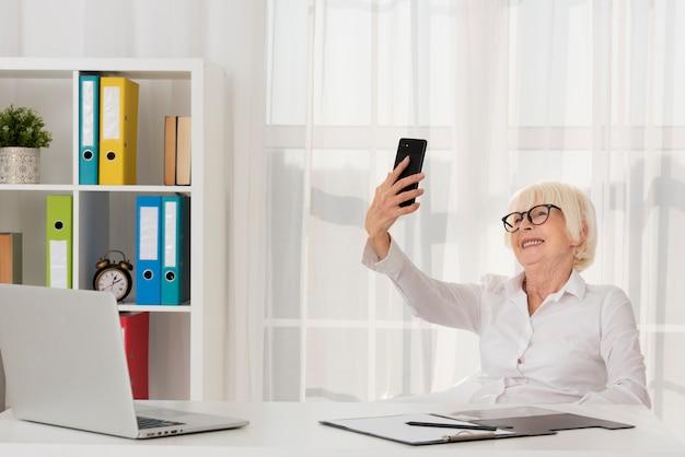 Oudste die met oogglazen de telefoon houdt Gratis Foto
