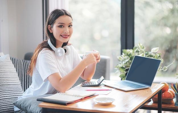 Oung de mooie aziatische kop van de vrouwenholding, glimlachend en bekijkend camera terwijl thuis het zitten en het werken met laptop in woonkamer. Premium Foto