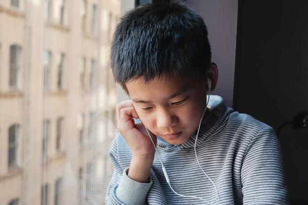 Oung mengde aziatisch preteen jongen thuis gebruikend digitale tablet Premium Foto