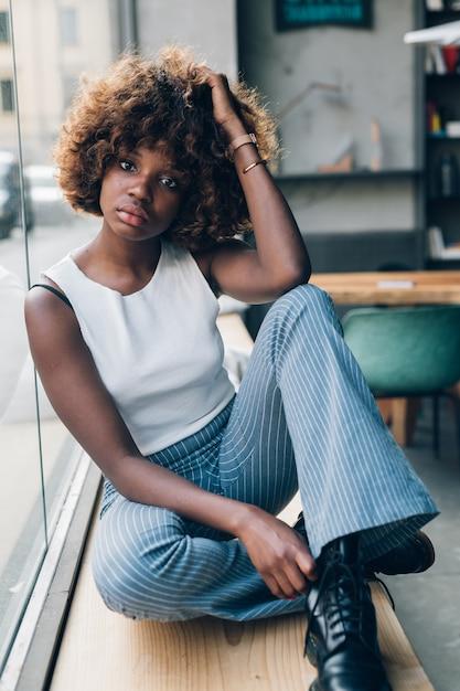 Oung zwarte vrouw die en camera stelt kijkt Premium Foto