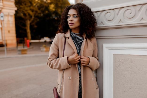 Outdoor fashion portret van glamour sensuele jonge stijlvolle zwarte dame trendy herfst outfit dragen, grijs fluwelen trui en beige wollen jas. Gratis Foto