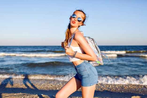 Outdoor lifestyle portret van grappig gelukkig meisje dat alleen naar de oceaan reist, glimlachend en geniet van zee strandtijd, gelukkige positieve emoties, gespiegelde zonnebril, witte crop top en rugzak, vreugde, beweging. Gratis Foto