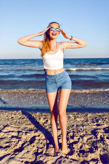 Outdoor lifestyle reizen portret van jonge blonde vrouw poseren in de buurt van de oceaan, crop top, mini denim hipster vintage shorty, rugzak en zonnebril, klaar voor avonturen, sexy gebruind lichaam, lange benen. Gratis Foto