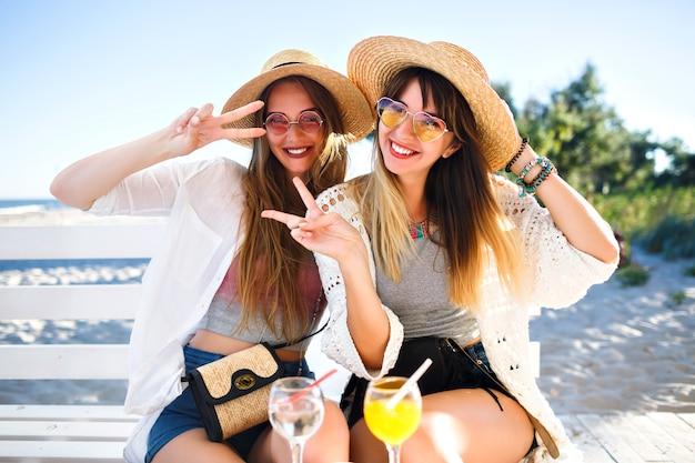 Outdoor portret van bedrijf gelukkig grappige hipster meisjes gek op het strand café, lekkere cocktails drinken lachen en glimlachen, vintage heldere boho zomeroutfits, relaties en plezier. Gratis Foto