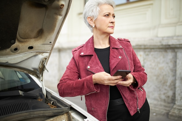 Outdoor portret van ernstige volwassen zakenvrouw in stijlvolle kleding poseren op haar kapotte auto met open kap, mobiele telefoon te houden Gratis Foto