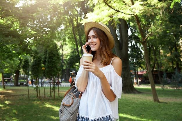 Outdoor portret van gelukkig mooie jonge vrouw draagt stijlvolle hoed, witte blouse en gestreepte rugzak, voelt zich ontspannen, praten op mobiele telefoon en afhaalmaaltijden koffie drinken in park in de zomer Gratis Foto