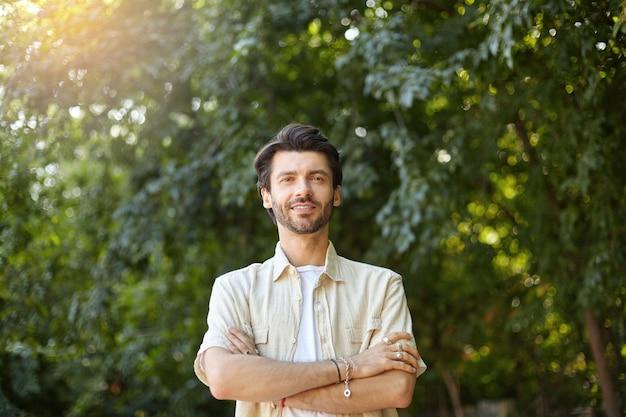 Outdoor portret van knappe jonge bebaarde man in beige overhemd poseren met gekruiste handen op zijn borst, op zoek met een lichte glimlach Gratis Foto