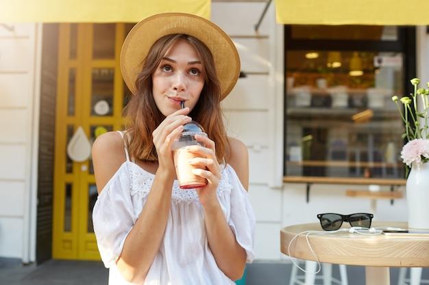 Outdoor portret van lachende aantrekkelijke jonge vrouw draagt stijlvolle zomerhoed en witte jurk, voelt zich gelukkig, wandelen in de stad en drinkt afhaalmaaltijden koffie Gratis Foto