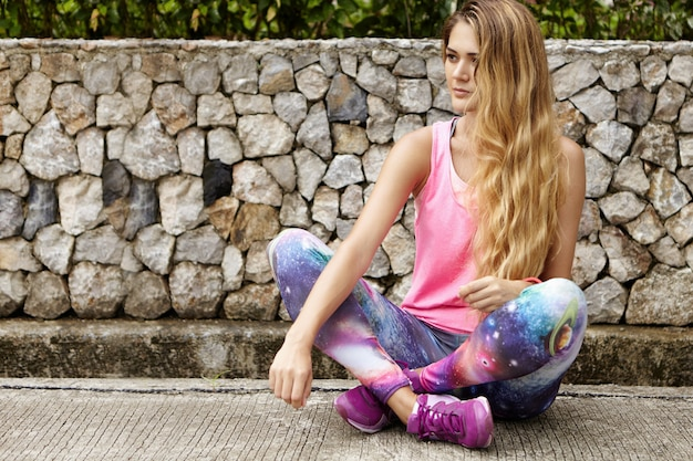 Outdoor portret van mooie blanke vrouw jogger met lang blond haar, gekleed in roze sporttop en ruimteprint legging zittend en ontspannen op stenen bestrating met benen gekruist na lange run Gratis Foto
