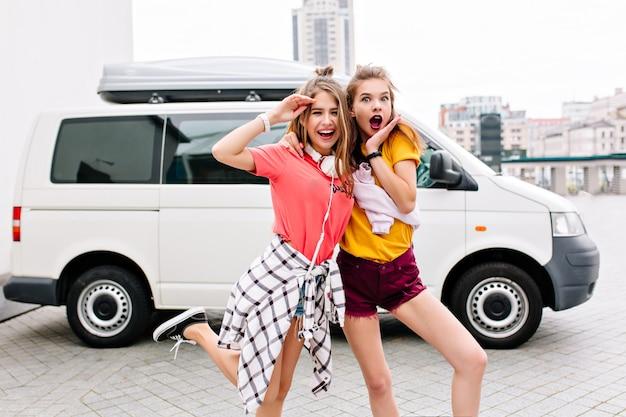 Outdoor portret van slanke stijlvolle vrienden grappig poseren naast witte auto met glimlach en verbaasd gezicht expressie Gratis Foto