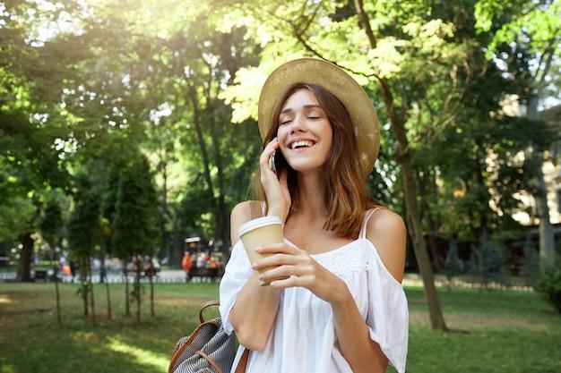 Outdoor portret van vrolijke aantrekkelijke jonge vrouw met gesloten ogen houden kopje afhaalmaaltijden koffie, draagt stijlvolle hoed, praten op mobiele telefoon en lachen in park in de zomer Gratis Foto