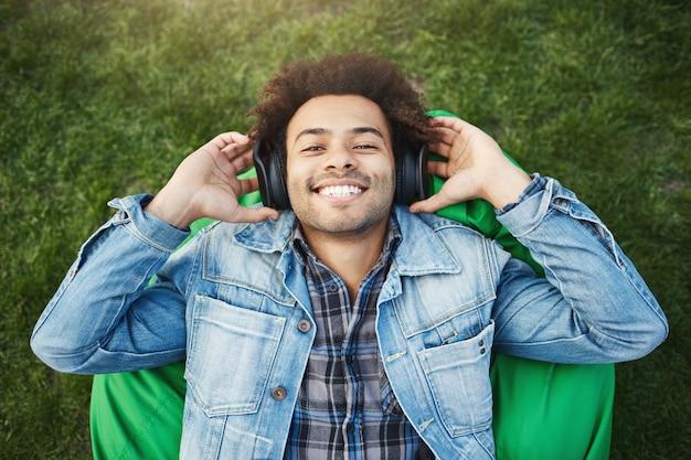 Outdoor portret van vrolijke vrolijke donkere man met borstelharen en afro kapsel liggend op zitzak stoel of gras, breed glimlachend terwijl het luisteren naar muziek via een koptelefoon en ze met de handen vasthoudt Gratis Foto