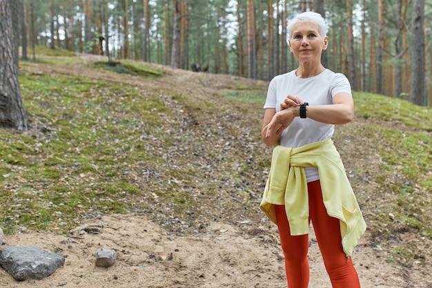 Outdoor portret van zelfverzekerde actieve vrouw van middelbare leeftijd in sportkleding met behulp van slimme horloge monitoring puls of hartslag tijdens het sporten in het park. Gratis Foto
