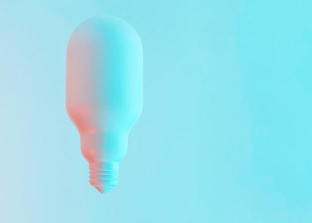Ovale witte vorm geschilderde gloeilamp tegen blauwe achtergrond Gratis Foto