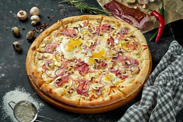 Ovengebakken italiaanse pizza met witte saus, kaas, ham, champignons en rauwe dooiers in een compositie met ingrediënten op een donkere tafel. uitzicht van boven. pizza carbonara Premium Foto
