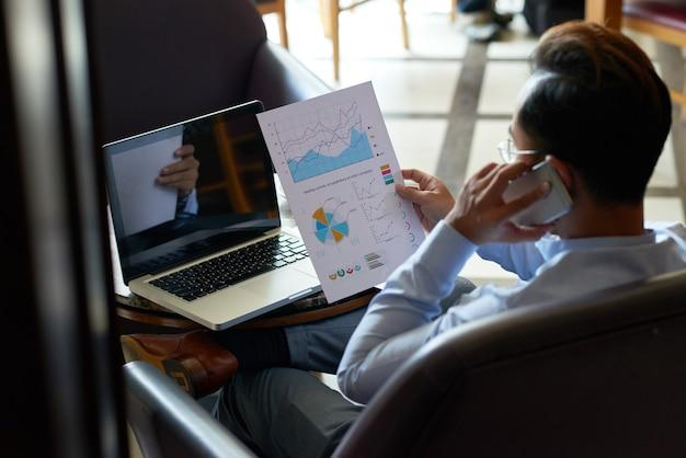 Over de schouder weergave van man multitasking herziening van financieel document en telefoongesprek Gratis Foto