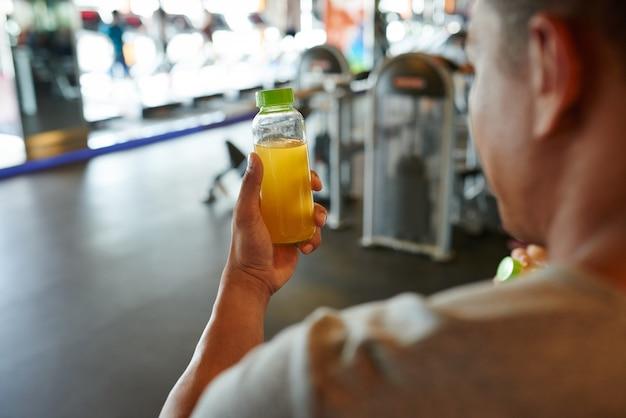 Over de schouder weergave van onherkenbare man met een fles sinaasappelsap Gratis Foto