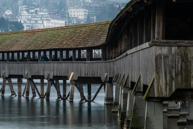 Overdekte brug in de buurt van de jezuïetenkerk van luzern, omringd door gebouwen in luzern in zwitserland Gratis Foto