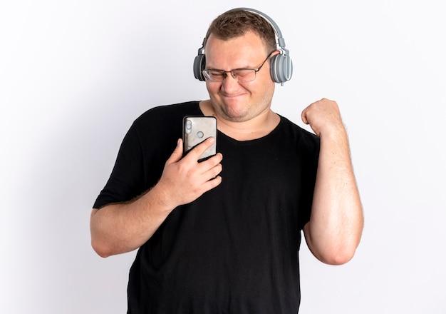 Overgewicht man in bril dragen zwart t-shirt met koptelefoon met smartphone genietend van zijn favoriete muziek staande over witte muur Gratis Foto