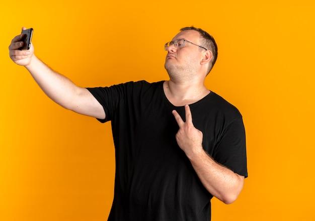 Overgewicht man in glazen dragen zwarte t-shirt met smartphone maken selfie weergegeven: overwinningsteken staande over oranje muur Gratis Foto