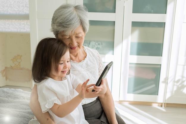Overgrootmoeder zit met achterkleindochter en kijkt in de smartphone. Premium Foto