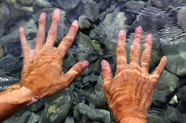 Overhandigt de golvende vormen van het rivierwater Premium Foto