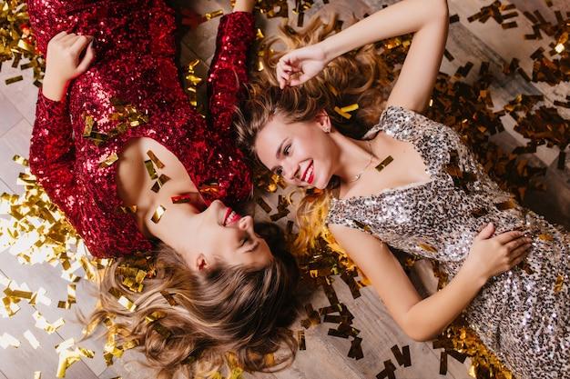 Overhead portret van geïnspireerde vrouwen draagt sprankelende kledij schattig lachend, terwijl ze rusten na een nieuwjaarsfeest Gratis Foto