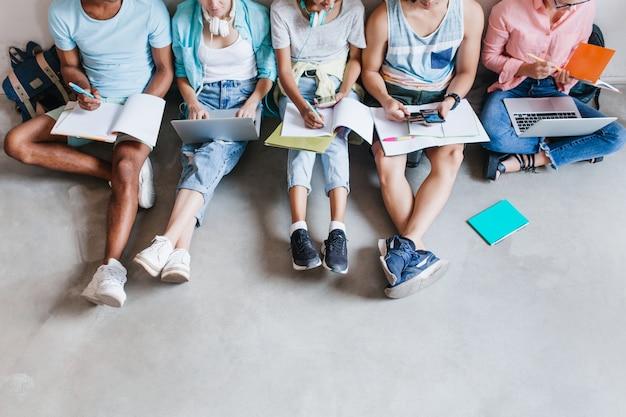 Overhead portret van studenten in trendy sneakers die chillen op de vloer terwijl ze zich samen voorbereiden op examens. universiteitsvrienden die samen tijd doorbrengen met behulp van laptops en abstract schrijven. Gratis Foto