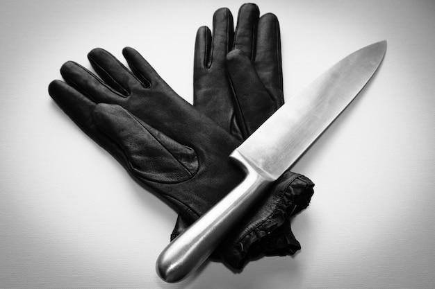 Overhead schot van een metalen mes over zwarte handschoenen op een wit oppervlak Gratis Foto