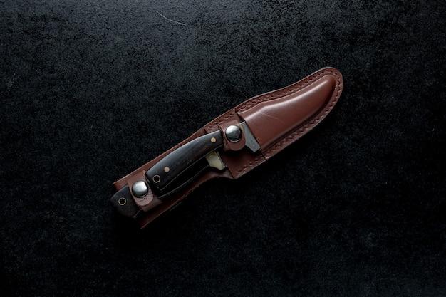 Overhead schot van twee vaste messen met bruin handvat in een bruine koffer op zwarte tafel Gratis Foto