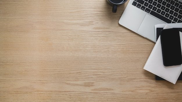Overhead schot van werkruimte met telefoon, laptop, kopie ruimte en andere kantoorbenodigdheden op houten tafel Premium Foto