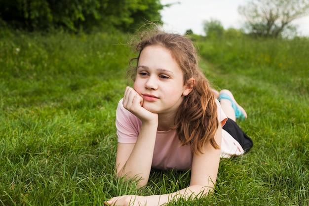Overweegt mooi meisje dat op groen gras bij park ligt Gratis Foto