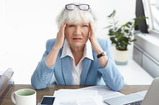 Overweldigd gefrustreerd volwassen oudere europese vrouwelijke accountant die formeel pak draagt met pijnlijke gestreste blik vanwege fout in financieel rapport, tempels masseren, hoofdpijn heeft Gratis Foto