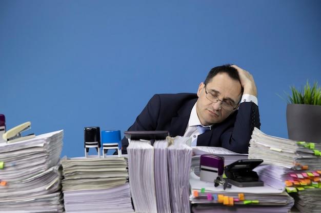 Overweldigde zakenman in slaap bij bureau vol papierwerk Premium Foto