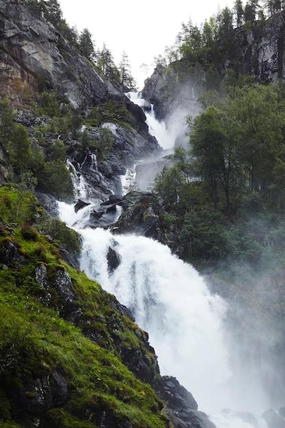 Overweldigende waterval met rotsen en bomen in noorwegen, scandinavië, europa Premium Foto