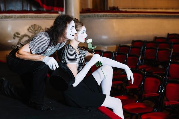 Overwogen paar mimespeler zittend op het podium in het auditorium Gratis Foto