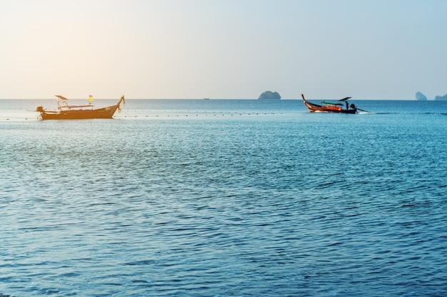 Overzeese zonsopgang of zonsondergang met vissersboot in ochtendlicht Premium Foto