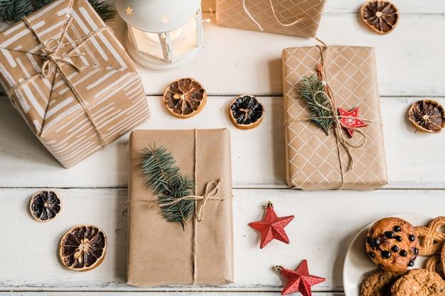 Overzicht van verpakte geschenkdozen, decoratieve schijfjes citroen, rode sterren, lantaarn en koekjes voor gasten op witte tafel Premium Foto